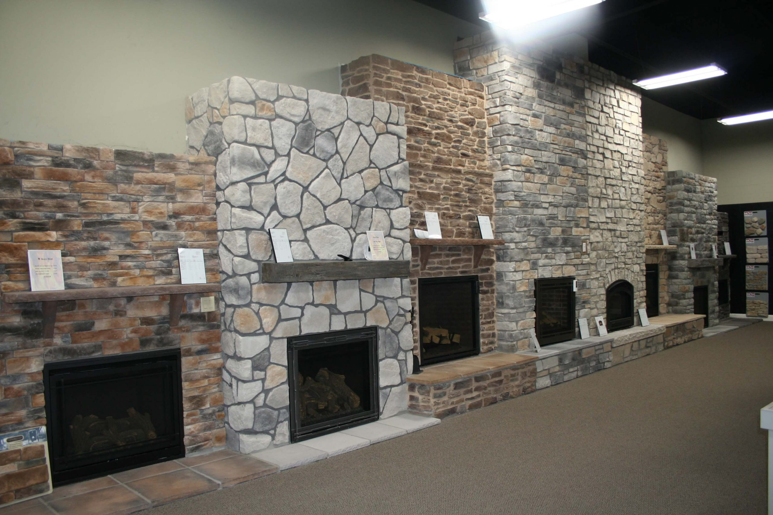 Stone fireplaces in showroom of Top Quality Building Products
